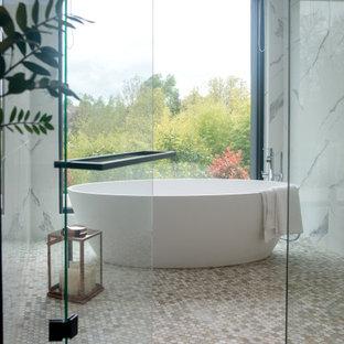Cette image montre une grand salle de bain principale design avec des portes de placard noires, une baignoire posée, un carrelage noir et blanc, du carrelage en marbre, un plan de toilette blanc et meuble-lavabo sur pied.
