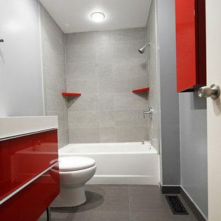 Immagine di una stanza da bagno per bambini moderna di medie dimensioni con ante lisce, ante rosse, vasca ad alcova, vasca/doccia, WC a due pezzi, piastrelle grigie, piastrelle in gres porcellanato, pareti blu, pavimento in gres porcellanato, lavabo integrato e top in superficie solida