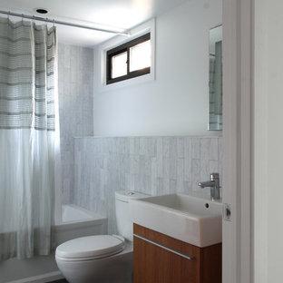 Idee per una stanza da bagno moderna con lavabo sospeso, ante lisce, ante in legno scuro, vasca ad alcova, vasca/doccia, WC a due pezzi e piastrelle bianche