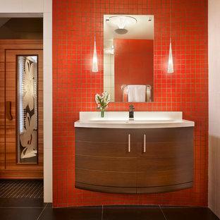 Imagen de cuarto de baño principal, moderno, de tamaño medio, con lavabo integrado, armarios con paneles lisos, puertas de armario marrones, encimera de acrílico, ducha a ras de suelo, sanitario de pared, baldosas y/o azulejos negros, baldosas y/o azulejos de porcelana, paredes rojas y suelo de baldosas de porcelana