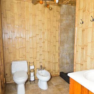 Immagine di una stanza da bagno tropicale con doccia alcova, bidè, piastrelle beige e pavimento con piastrelle in ceramica