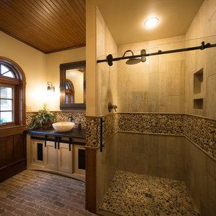 Immagine di una stanza da bagno stile rurale di medie dimensioni con ante in stile shaker, ante beige, doccia alcova, piastrelle multicolore, piastrelle di ciottoli, pareti beige, pavimento in mattoni, lavabo a bacinella, top in cemento, pavimento multicolore e porta doccia scorrevole