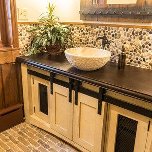 Foto di una stanza da bagno stile rurale di medie dimensioni con ante in stile shaker, ante beige, piastrelle beige, piastrelle di ciottoli, pareti beige, pavimento in mattoni, lavabo a bacinella, top in cemento e pavimento multicolore