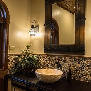 Diseño de cuarto de baño rural, de tamaño medio, con armarios estilo shaker, puertas de armario beige, baldosas y/o azulejos multicolor, suelo de baldosas tipo guijarro, paredes beige, lavabo sobreencimera y encimera de cemento