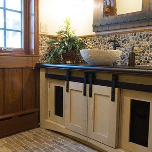 Foto di una stanza da bagno stile rurale di medie dimensioni con ante in stile shaker, ante beige, piastrelle multicolore, piastrelle di ciottoli, pareti beige, pavimento in mattoni, lavabo a bacinella, top in cemento e pavimento multicolore