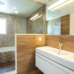 Modernes Badezimmer mit integriertem Waschbecken, flächenbündigen Schrankfronten, weißen Schränken, Mineralwerkstoff-Waschtisch, Badewanne in Nische, Duschbadewanne, Toilette mit Aufsatzspülkasten, braunen Fliesen und Fliesen in Holzoptik in New York