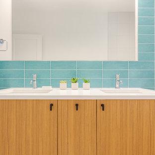 デンバーの小さいモダンスタイルのおしゃれな子供用バスルーム (フラットパネル扉のキャビネット、淡色木目調キャビネット、ドロップイン型浴槽、シャワー付き浴槽、一体型トイレ、青いタイル、セラミックタイル、白い壁、セラミックタイルの床、アンダーカウンター洗面器、クオーツストーンの洗面台、白い床、シャワーカーテン) の写真