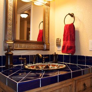 Mittelgroßes Klassisches Badezimmer En Suite mit Schrankfronten mit vertiefter Füllung, hellbraunen Holzschränken, Duschnische, Wandtoilette mit Spülkasten, blauen Fliesen, Keramikfliesen, beiger Wandfarbe, Terrakottaboden, Einbauwaschbecken, gefliestem Waschtisch, rotem Boden, Falttür-Duschabtrennung und blauer Waschtischplatte in Denver