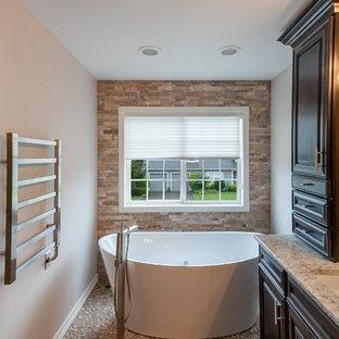 シアトルの中サイズのトランジショナルスタイルのおしゃれなマスターバスルーム (レイズドパネル扉のキャビネット、濃色木目調キャビネット、置き型浴槽、アルコーブ型シャワー、分離型トイレ、マルチカラーのタイル、石タイル、グレーの壁、玉石タイル、アンダーカウンター洗面器、珪岩の洗面台、グレーの床、開き戸のシャワー、マルチカラーの洗面カウンター) の写真