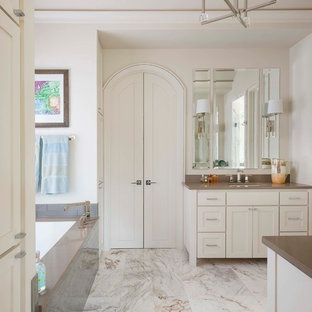 Imagen de cuarto de baño principal, clásico renovado, con armarios estilo shaker, puertas de armario blancas, bañera encastrada sin remate, paredes blancas, lavabo bajoencimera, baldosas y/o azulejos grises y encimeras grises