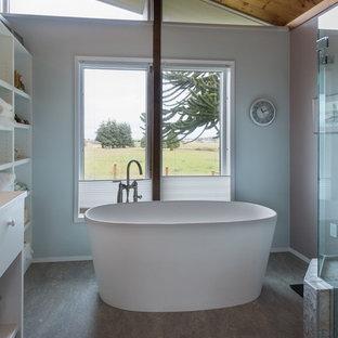 Imagen de cuarto de baño principal, tradicional renovado, de tamaño medio, con armarios con paneles lisos, puertas de armario blancas, encimera de acrílico, bañera exenta, ducha empotrada, suelo de linóleo y paredes blancas