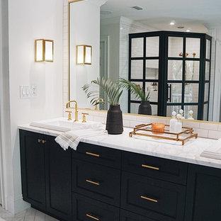 Ispirazione per una grande stanza da bagno padronale chic con ante con riquadro incassato, ante nere, doccia ad angolo, piastrelle bianche, piastrelle in ceramica, pareti bianche, pavimento in marmo, lavabo da incasso, top in marmo, pavimento grigio, porta doccia a battente e top bianco