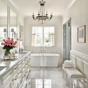 Источник вдохновения для домашнего уюта: большая главная ванная комната в средиземноморском стиле с отдельно стоящей ванной, мраморным полом, фасадами с утопленной филенкой, белыми фасадами, белыми стенами, врезной раковиной, серым полом, серой столешницей, тумбой под две раковины, встроенной тумбой и панелями на стенах