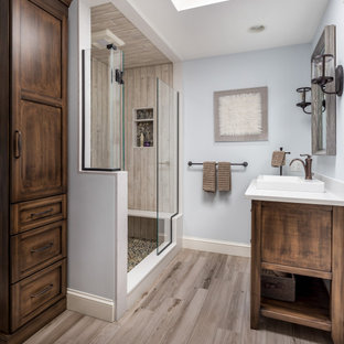 Example of a mid-sized transitional master brown tile and porcelain tile porcelain floor and brown floor alcove shower design in Boston with flat-panel cabinets, a one-piece toilet, a drop-in sink, quartz countertops, a hinged shower door, white countertops, medium tone wood cabinets and blue walls