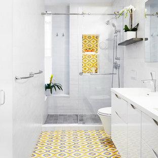 Inspiration för moderna badrum med dusch, med släta luckor, vita skåp, en vägghängd toalettstol, gul kakel, grå kakel, flerfärgad kakel, vit kakel, cementkakel, vita väggar, cementgolv, bänkskiva i akrylsten, en dusch i en alkov och dusch med skjutdörr