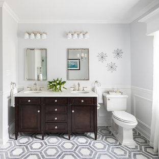 Large elegant master white tile and ceramic tile marble floor, gray floor, double-sink and wainscoting bathroom photo in New York with shaker cabinets, dark wood cabinets, an undermount sink, quartz countertops, white countertops, a two-piece toilet, gray walls, a hinged shower door and a freestanding vanity