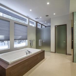 Foto di una stanza da bagno padronale minimalista di medie dimensioni con ante lisce, ante in legno bruno, vasca idromassaggio, doccia doppia, piastrelle verdi, piastrelle di vetro, pareti grigie, parquet chiaro, lavabo integrato e top in superficie solida