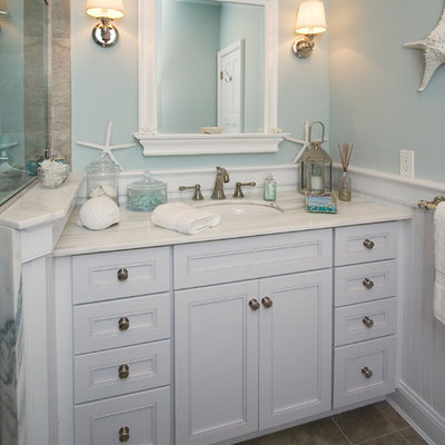 Example of a beach style beige tile bathroom design in New York with an undermount sink, recessed-panel cabinets and white cabinets