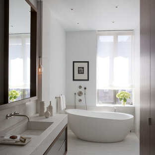 Freestanding bathtub - contemporary freestanding bathtub idea in New York with an integrated sink, flat-panel cabinets and dark wood cabinets