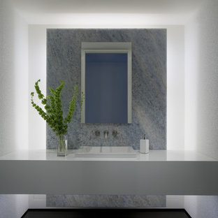 Design ideas for a contemporary bathroom in New York with a built-in sink, flat-panel cabinets and white cabinets.