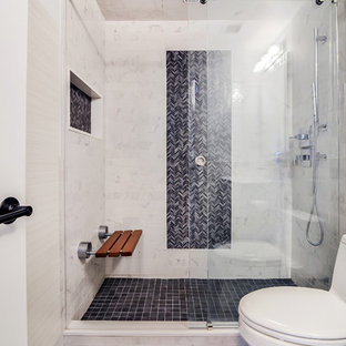This is an example of a mid-sized transitional master bathroom in New York with an alcove shower, a one-piece toilet, gray tile, white tile, ceramic tile, ceramic floors, flat-panel cabinets, white cabinets, white walls, solid surface benchtops, a sliding shower screen, a niche and a shower seat.