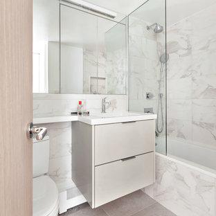 Kleines Modernes Badezimmer mit flächenbündigen Schrankfronten, grauen Schränken, Badewanne in Nische, Duschbadewanne, grauen Fliesen, Porzellanfliesen, Marmorboden, Unterbauwaschbecken, Mineralwerkstoff-Waschtisch, grauem Boden, weißer Waschtischplatte und offener Dusche in New York