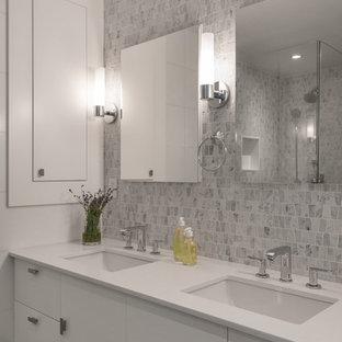 Diseño de cuarto de baño principal, actual, grande, con baldosas y/o azulejos grises, baldosas y/o azulejos en mosaico, paredes grises, armarios con paneles lisos, puertas de armario blancas, lavabo bajoencimera, ducha esquinera, suelo de madera oscura, encimera de acrílico, suelo marrón y ducha con puerta con bisagras