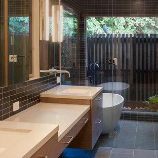 Ispirazione per una stanza da bagno padronale minimalista con lavabo sottopiano, ante lisce, ante bianche, vasca freestanding, vasca/doccia, piastrelle nere, piastrelle in ceramica, pareti bianche e pavimento con piastrelle in ceramica