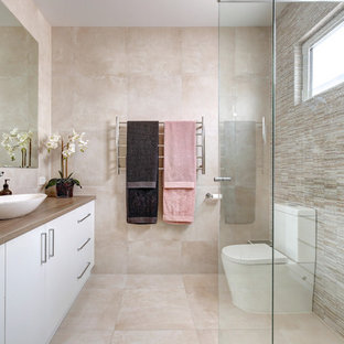Design ideas for a mid-sized contemporary 3/4 bathroom in Adelaide with flat-panel cabinets, white cabinets, a corner shower, a one-piece toilet, beige tile, beige walls, a vessel sink, wood benchtops, beige floor and brown benchtops.