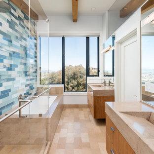 Cette photo montre une douche en alcôve principale tendance de taille moyenne avec un lavabo intégré, un placard à porte plane, des portes de placard en bois brun, une baignoire encastrée, un carrelage multicolore, un mur blanc, un carrelage en pâte de verre et un plan de toilette en calcaire.