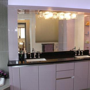 Esempio di una stanza da bagno padronale minimalista con ante di vetro, piastrelle di cemento, pareti beige, lavabo sottopiano e top in quarzite
