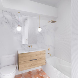 Inspiration for a mid-sized eclectic white tile and marble tile cement tile floor and pink floor bathroom remodel in New York with flat-panel cabinets, light wood cabinets, a one-piece toilet, white walls, a wall-mount sink, solid surface countertops and white countertops