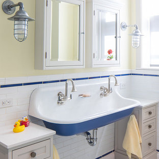 Coastal blue tile, white tile and subway tile mosaic tile floor and white floor bathroom photo in New York with shaker cabinets, beige cabinets, yellow walls and a trough sink