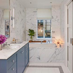 Modern inredning av ett mellanstort vit vitt en-suite badrum, med ett undermonterad handfat, släta luckor, blå skåp, ett undermonterat badkar, vit kakel, vita väggar, stenhäll, marmorbänkskiva och vitt golv