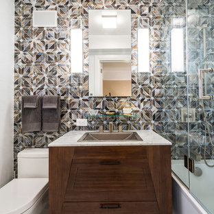 Bathroom - mid-sized contemporary 3/4 multicolored tile and mosaic tile ceramic floor bathroom idea in New York with a drop-in sink, furniture-like cabinets, dark wood cabinets, white walls, a two-piece toilet and marble countertops