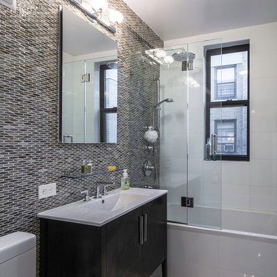 Inspiration for a mid-sized contemporary 3/4 gray tile and mosaic tile porcelain tile bathroom remodel in New York with black cabinets, a two-piece toilet, gray walls, an integrated sink and flat-panel cabinets