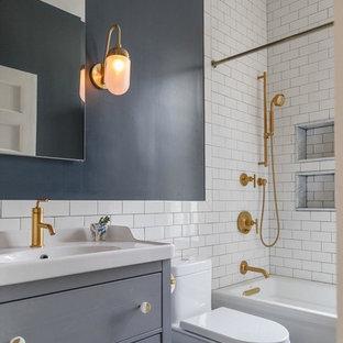 Modelo de cuarto de baño tradicional renovado con armarios con paneles lisos, puertas de armario grises, bañera esquinera, combinación de ducha y bañera, baldosas y/o azulejos blancos, baldosas y/o azulejos de cemento, paredes azules, lavabo tipo consola, suelo azul y ducha con cortina
