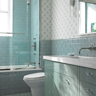 Contemporary bathroom in New York with flat-panel cabinets, blue cabinets, an alcove tub, a shower/bathtub combo, blue tile and white benchtops.