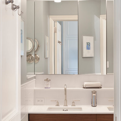 Inspiration for a mid-sized transitional master white tile and stone tile mosaic tile floor and gray floor alcove shower remodel in New York with flat-panel cabinets, medium tone wood cabinets, a wall-mount toilet, white walls, an undermount sink, glass countertops and a hinged shower door