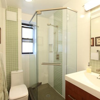 Corner shower - small eclectic 3/4 green tile and porcelain tile porcelain tile corner shower idea in New York with flat-panel cabinets, medium tone wood cabinets, a one-piece toilet, white walls, a trough sink and solid surface countertops