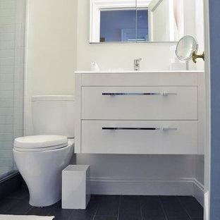 Modern inredning av ett litet badrum med dusch, med ett väggmonterat handfat, släta luckor, vita skåp, en hörndusch, vit kakel, tunnelbanekakel, vita väggar, en toalettstol med separat cisternkåpa och vinylgolv