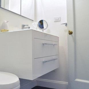 Ejemplo de cuarto de baño con ducha, moderno, pequeño, con lavabo suspendido, armarios con paneles lisos, puertas de armario blancas, encimera de vidrio, ducha esquinera, baldosas y/o azulejos de cemento, paredes blancas, sanitario de dos piezas, baldosas y/o azulejos blancos y suelo vinílico