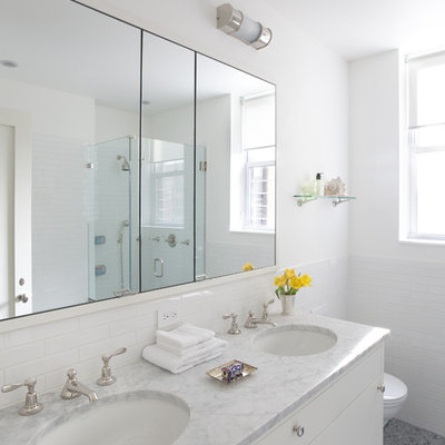 Inspiration for a mid-sized contemporary 3/4 subway tile mosaic tile floor and gray floor corner shower remodel in New York with marble countertops, flat-panel cabinets, white cabinets, white walls, an undermount sink and a hinged shower door