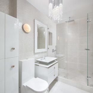 Immagine di una grande stanza da bagno padronale minimalista con ante lisce, ante bianche, doccia alcova, WC monopezzo, piastrelle beige, piastrelle in ceramica, pareti beige, pavimento con piastrelle in ceramica, lavabo a bacinella, top in vetro, pavimento beige e porta doccia a battente