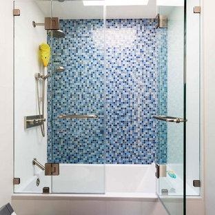 Ispirazione per una stanza da bagno con doccia chic di medie dimensioni con WC monopezzo, pareti bianche, vasca ad alcova, doccia alcova, piastrelle blu, piastrelle a mosaico e porta doccia a battente