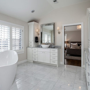 Inspiration for a mid-sized transitional master white tile ceramic tile and white floor freestanding bathtub remodel in Denver with shaker cabinets, white cabinets, white walls, granite countertops, a vessel sink and gray countertops