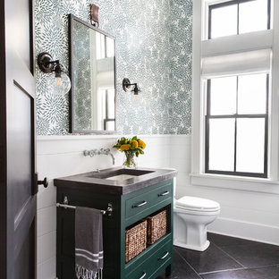 This is an example of a large rural shower room in New York with recessed-panel cabinets, green cabinets, a two-piece toilet, green walls, limestone flooring, a submerged sink, concrete worktops and black floors.