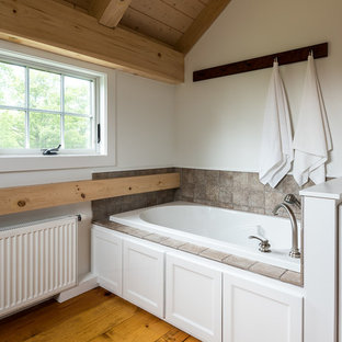 Idee per una stanza da bagno padronale country di medie dimensioni con ante con riquadro incassato, ante bianche, vasca idromassaggio, pareti bianche, parquet chiaro, top in legno e pavimento giallo
