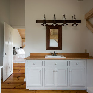 Mid-sized farmhouse master light wood floor and yellow floor bathroom photo in New York with recessed-panel cabinets, white cabinets, white walls and wood countertops