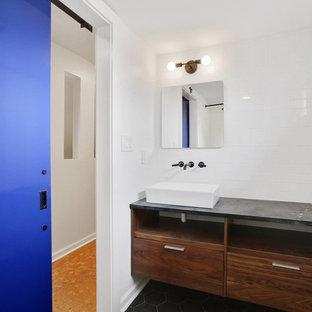 Foto de cuarto de baño minimalista, pequeño, con armarios con paneles lisos, puertas de armario de madera oscura, baldosas y/o azulejos grises, paredes blancas, lavabo sobreencimera y encimera de esteatita